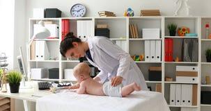 Молодой доктор играя с младенцем и показывая большой палец руки вверх на камере в офисе акции видеоматериалы