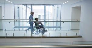 Молодой доктор нажимая пациента в кресло-коляске в больнице 4k сток-видео