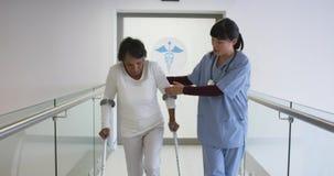 Молодой доктор помогая терпеливым костылям пользы в больнице 4k сток-видео