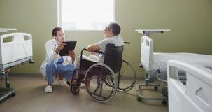Молодой доктор разговаривая с пациентом в кресло-коляске 4k видеоматериал