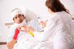Молодой доктор рассматривая раненого пациента стоковые фотографии rf