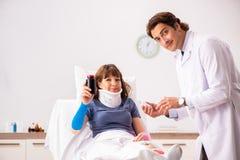 Молодой доктор рассматривая раненого пациента стоковое изображение