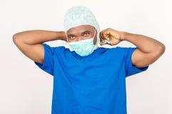 Молодой доктор связывая его маску перед деятельностью стоковое фото rf