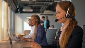 Молодой дружелюбный агент женщины оператора при шлемофоны работая в центре телефонного обслуживания акции видеоматериалы