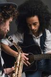 молодой дуэт музыкантов играя саксофон и акустическую гитару стоковое изображение rf
