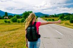 Молодой женский автостопщик дорогой стоковое фото