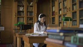 Молодой женский азиатский студент в белой рубашке слушая к музыке видеоматериал