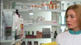Молодой женский аптекарь идя в аптеку, проверяя продукты в списке сток-видео