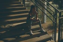 Молодой женский бегун отдыхая на лестницах стоковые фотографии rf