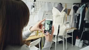 Молодой женский блоггер дизайна одежды снимает портняжничающ куклу при полу-законченная одежда прикалыванная к нему Съемка конца- сток-видео