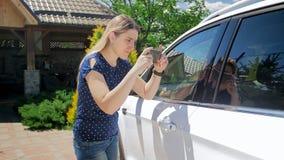 Молодой женский водитель принимая фото ее автомобиля для продавать его онлайн стоковые изображения rf