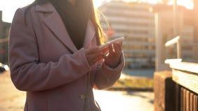 Молодой женский вызывать на положении смартфона на sunlit улице, деля эмоции стоковые изображения