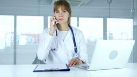 Молодой женский доктор говоря на телефоне в больнице сток-видео