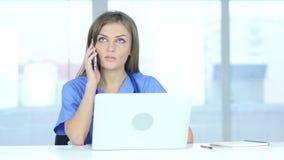 Молодой женский доктор говоря на телефоне в больнице акции видеоматериалы