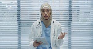 Молодой женский доктор используя планшет и говорить к камере 4k сток-видео