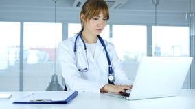Молодой женский доктор печатая на компьтер-книжке в больнице стоковые фотографии rf