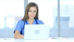 Молодой женский доктор печатая на компьтер-книжке в больнице стоковые изображения