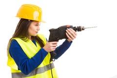 Молодой женский инженер используя сверля машину стоковая фотография