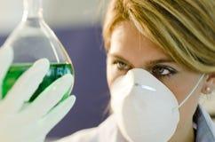 Молодой женский исследователь работая с beaker Стоковые Фото