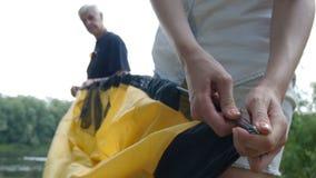 Молодой женский и пожилой мужчина выбыл туриста кладя вверх по шатру Зеленый туризм, Женские руки закрывают вверх сток-видео