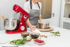 Молодой женский кондитер взбивает сливк в шаре металла в красном электрическом смесителе Концепция домодельного печенья, варя стоковая фотография rf