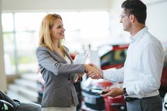 Молодой женский консультант продаж автомобиля работая в выставочном зале стоковое фото