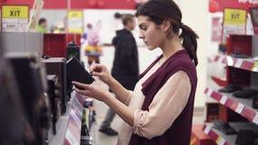 Молодой женский костюм выбирая аудиосистему от разнообразия в магазине электроники Рассматривать тщательно дикторов на a акции видеоматериалы
