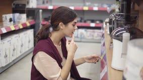 Молодой женский костюм рассматривая пластмасовые контейнеры для электрического juicer ища совершенный качественный kitchenware вн сток-видео