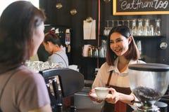 Молодой женский кофе сервировки barista к клиенту в кафе стоковое изображение rf