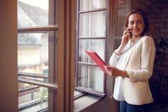 Молодой женский менеджер на сотовом телефоне в компании Стоковое Изображение RF