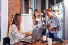Молодой женский менеджер сидя на столе указывая на компьтер-книжку объясняя давать задает работу к ее работникам стоять запись Стоковые Изображения