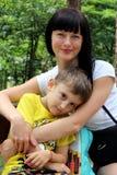 Молодой женский модельный усмехаться пока смотрящ камеру, сидя на стенде в парке с ее маленьким сыном стоковые фото