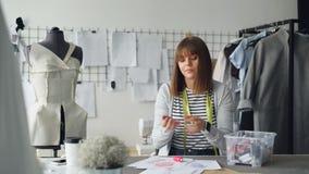 Молодой женский портной занятый выбрать цвет новой одежды нарисованный на эскизе Она выбирает различные катушкы от коробки и видеоматериал