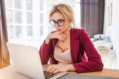 Молодой женский предприниматель сидя на таблице в ее домашнем офисе р стоковое фото rf
