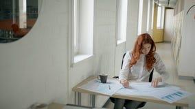 Молодой женский профессионал работает с светокопией, чертежом, усаживанием на рабочем месте в компании сток-видео