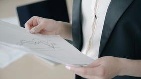Молодой женский профессионал смотрит документы стоя в современном офисе сток-видео
