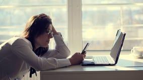 Молодой женский работник офиса клерка просматривает социальные сети на мобильном телефоне, во время ее дня работы, в офисе коротк