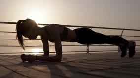 Молодой женский силуэт делая тренировку планки на взморье тело сильное сумрак Голубое утро сток-видео