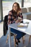 Молодой женский студент девушки в стеклах усмехается с кофе бумажного стаканчика Стоковые Фото