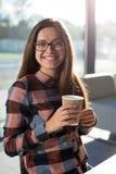 Молодой женский студент девушки в стеклах усмехается с кофе бумажного стаканчика Стоковая Фотография RF