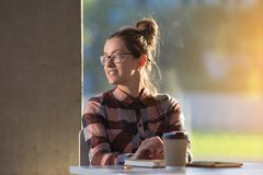 Молодой женский студент девушки в стеклах усмехается с кофе бумажного стаканчика Стоковые Изображения RF