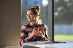 Молодой женский студент девушки в стеклах усмехается с кофе бумажного стаканчика Стоковое Изображение