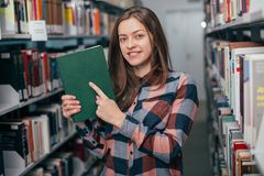 Молодой женский студент девушки усмехаясь с книгой в библиотеке Стоковое Изображение RF
