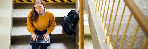 Молодой женский студент колледжа сидя на лестницах на школе, писать эссе на ее компьтер-книжке и смотря вверх на камере Образован стоковое фото