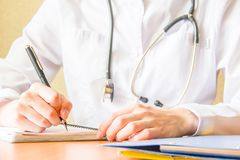 Молодой женский студент-медик используя современный smartphone в больнице, писать в тетради Конец вверх по всходу рук стоковые фото