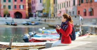 Молодой женский турист наслаждаясь взглядом Vernazza, одной из 5 столети-старых деревень Cinque Terre, расположенных на изрезанно стоковое фото