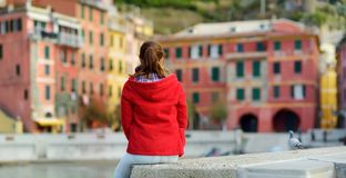 Молодой женский турист наслаждаясь взглядом Vernazza, одной из 5 столети-старых деревень Cinque Terre, расположенных на изрезанно стоковые изображения