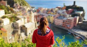 Молодой женский турист наслаждаясь взглядом Vernazza, одной из 5 столети-старых деревень Cinque Terre, расположенных на изрезанно стоковое фото rf