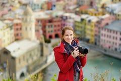 Молодой женский турист наслаждаясь взглядом Vernazza, одной из 5 столети-старых деревень Cinque Terre, расположенных на изрезанно стоковая фотография