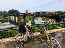 Молодой женский турист на ее велосипеде наслаждаясь взглядом моста над рекой Kwai стоковая фотография